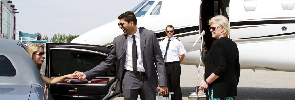 Fully vetted and trusted chauffeur in a suit and tie helping a smiling, professional woman out of a car with private jet and trusted pilot in the background.