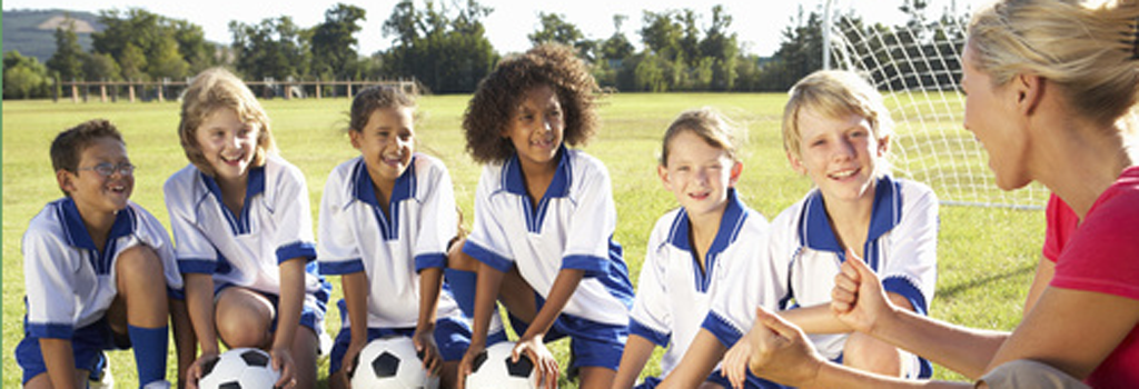 Youth group soccer players in blue and white uniforms smiling at female coach who was hired after receiving a cleared background check.